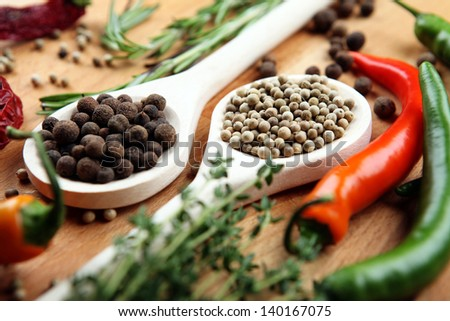 A handful of white and black pepper peas in a wooden spoon on a wooden board
