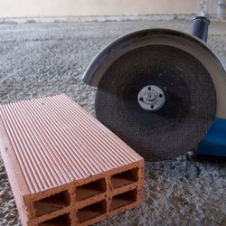 a handheld radial saw, useful for cutting building materials; and a brick on a rough concrete floor.