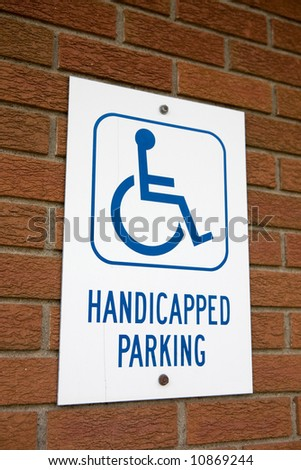 A handicapped parking sign on a brick wall