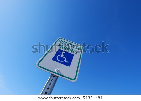 "A ""Handicapped Parking"" sign shot from a dynamic angle against a brilliant blue sky.  Enough space for your ad copy."