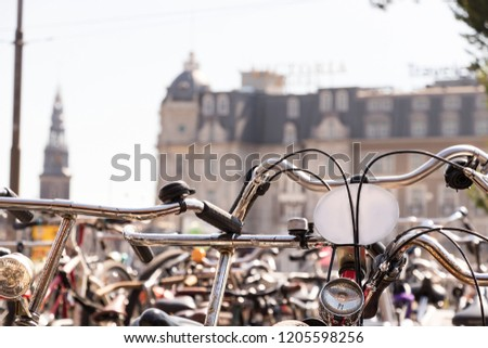A handlebar of a bike parked with hundred of bicycles in Amsterdam.