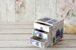 A handmade chest of trinket drawers decoupaged with vintage paper with pots of Lavender on a rustic wooden background