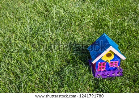 A handmade, colorful, brightly painted bird house resembling a family home in the bottom corner of a green lawn in bright sunshine. #1241791780