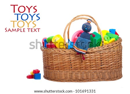 A handmade doll with  sitting on a pile of toys isolated on white background.