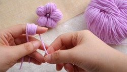 A handmade flower made out of yarn ball by wrapping the yarns around the finger
