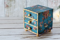 A handmade mini chest of three drawers decoupaged with blue floral vintage paper and gold leaf