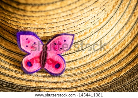 A handmade pink felt butterfly sits on a straw women's hat on the left. Close-up, nobody, summertime