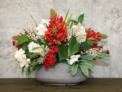A handmade silk flower center piece arrangement with red and ivory flowers and green filler leaves.