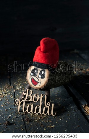 a handmade tio de nadal, a typical christmas character of catalonia, spain, and the text bon nadal, merry christmas written in catalan, on a gray rustic wooden surface, slightly lighted Zdjęcia stock ©