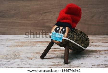 a handmade tio de nadal, a typical christmas character of catalonia, spain, wearing a face mask, on a white rustic wooden surface Zdjęcia stock ©