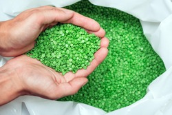A hands hold or touching biodegradable plastic pellets, plastic polymer dye granules color clear green