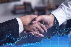 A handshake as a symbol of successful transaction on brokerage services at international investment bank. Capital market, stock trading. Financial hologram chart. Women in business.