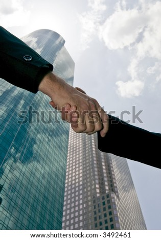 A handshake between a man and woman with tall beautiful glass towers of commerce in the background.