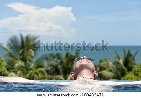 A handsome adult male lies chilled in a jacuzzi at a luxurious exotic spa resort.