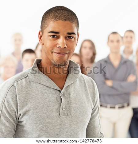 A handsome African-American man posing in front of a group of people.