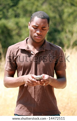 a handsome african american man thinks and responds while he text messages on his cell phone