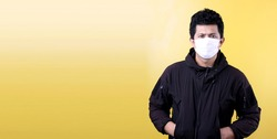A handsome  Asian man wearing a parka and wearing a mask isolated on yellow background in studio With copy space for ads.