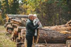 A handsome bald father kissing his small daughter in a autumn forest against the background of stacked logs on background in a autumn forest. Horizontal view