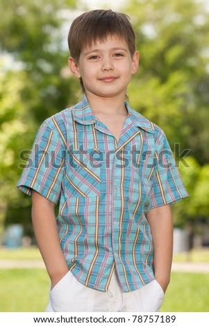 A handsome boy is standing in the park on the green grass