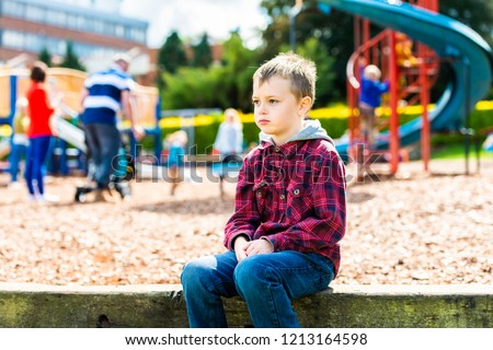 A handsome boy with ADHD, Autism, Asperger Syndrome sitting at the park, scared and apprehensive about playing with the other children, looking nervous and apprehensive