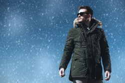 A handsome brutal man wearing a parka and sunglasses. Fashion for men. Autumn, winter.