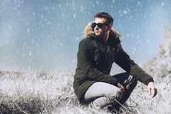 A handsome brutal man wearing a parka and sunglasses in the countryside. Fashion for men. Autumn, winter.
