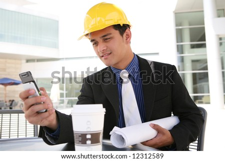 A handsome business construction man looking at cell phone - stock photo