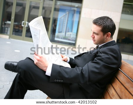 A handsome business man at his company office building reading newspaper