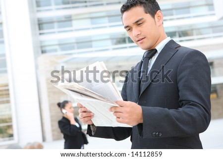 A handsome business man reading the newspaper at office building
