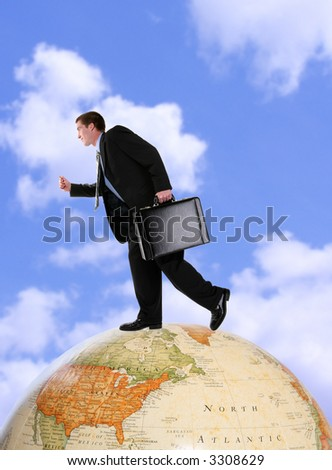 A handsome business man running on a world globe