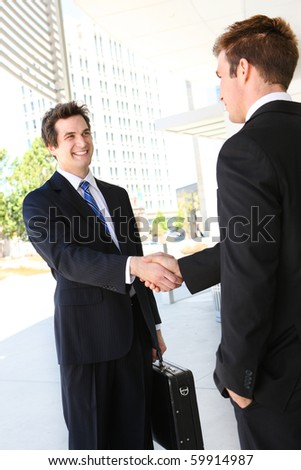 A handsome business man team  shaking hands outside office