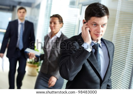 A handsome businessman calling by the phone in office - stock photo