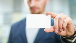 A handsome businessman showing a blank piece of paper. Close-up shot. Soft focus.