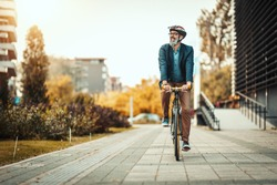 A handsome casual middle-aged businessman is going to the office by bicycle. He is driving bike in front of office district.