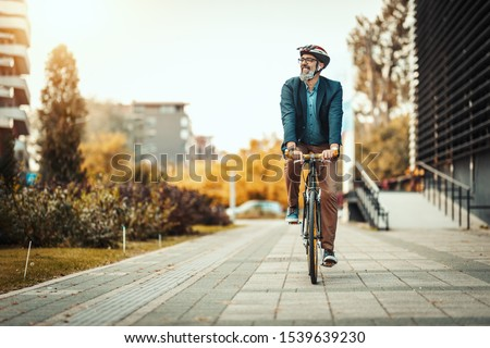 Photo of  A handsome casual middle-aged businessman is going to the office by bicycle. He is driving bike in front of office district.