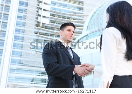 A handsome caucasian business man shaking hands with woman