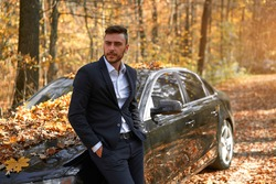 A handsome Caucasian man wearing business suit standing near black car on nature.  Young adult businessman travels by car on a beautiful sunny autumn day. Elite luxury driver.