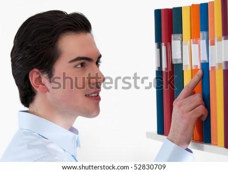 A handsome collage student  searching among colorful binders against white background