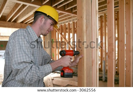 A handsome construction man using a drill to secure a beam