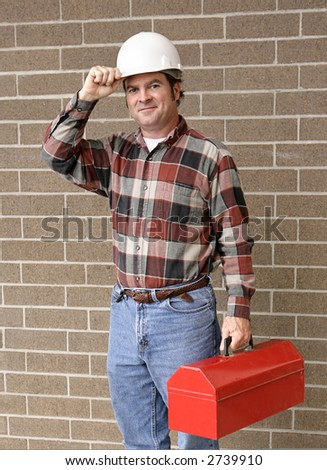 A handsome construction worker carrying his toolbox and tipping his hard hat.