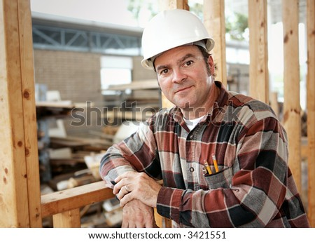 A handsome construction worker leaning on the frame of a building he's working on. Authentic construction worker photographed on site. - stock photo