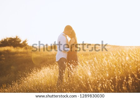A handsome couple hugging and kissing on the top of hill, on sunset #1289830030