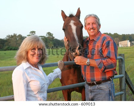 A handsome farm couple posing with their favorite horse.