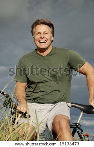 A handsome fit forties man takes a break during a bike ride in the countryside while dark storm clouds roll in behind him.He has a fabulous smile.