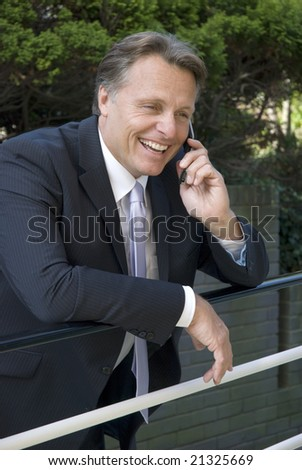 a handsome forties businessman enjoys a friendly chat on his cellphone while leaning on some railings
