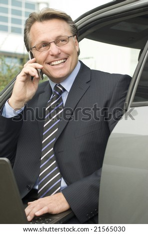 A handsome forties businessman wearing spectacles is sitting in his car with his laptop while enjoying a friendly chat on his cellphone