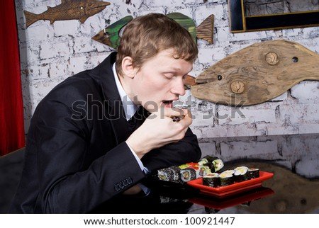 A handsome guy in the restaurant eats sushi