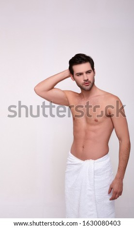 A handsome guy is standing wrapped in a white towel on his lower back, thoughtfully scratching his head and looking to the side. Beauty concept, body skin care. Beautiful people.