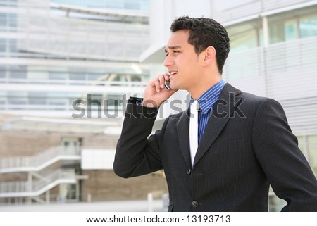A handsome hispanic business man on the phone in front of office building