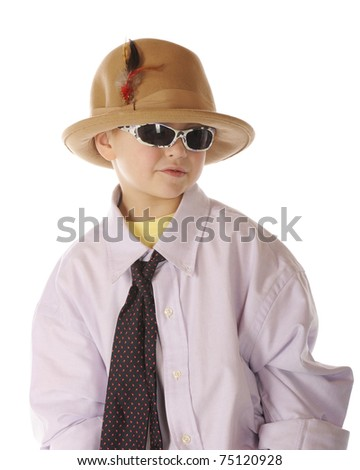 A handsome kindergarten boy with sunglasses, dressing up in Grandpa's shirt, tie and hat.  Isolated on white.